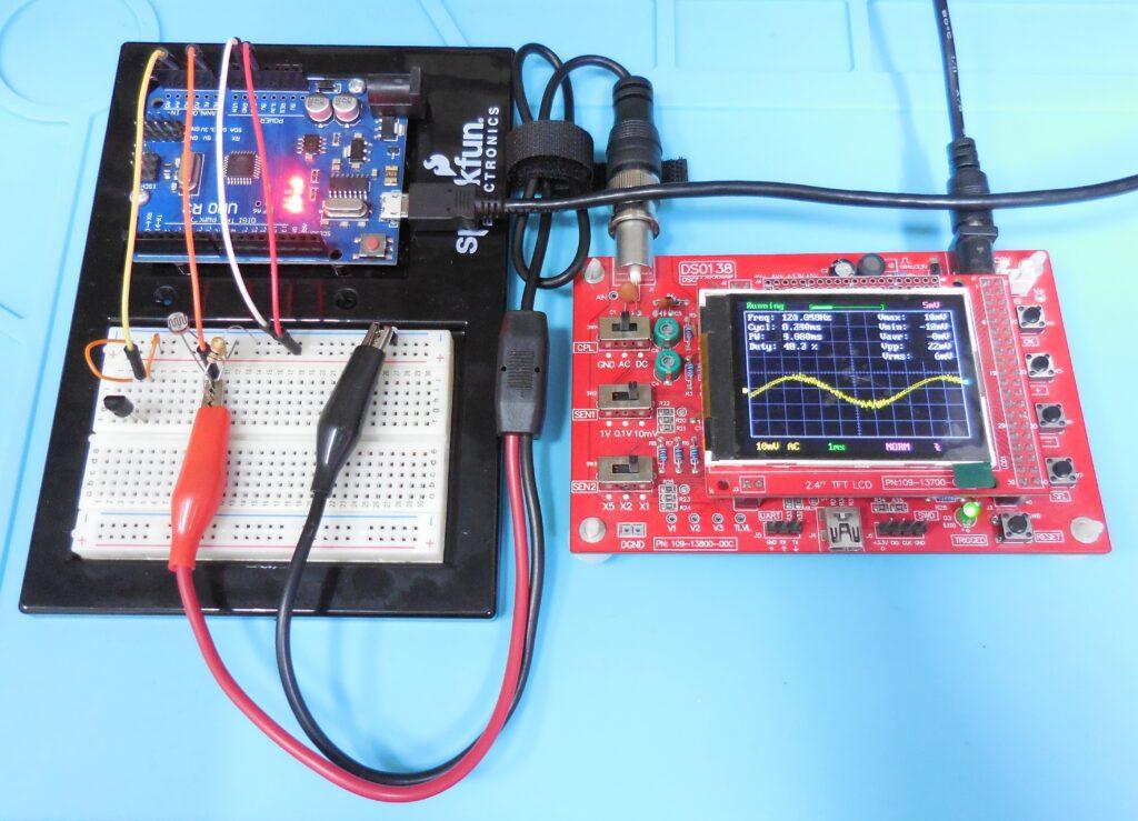 Fotografia do circuito de ensaio ligado ao osciloscópio mostrando na tela o sinal do sensor de luz